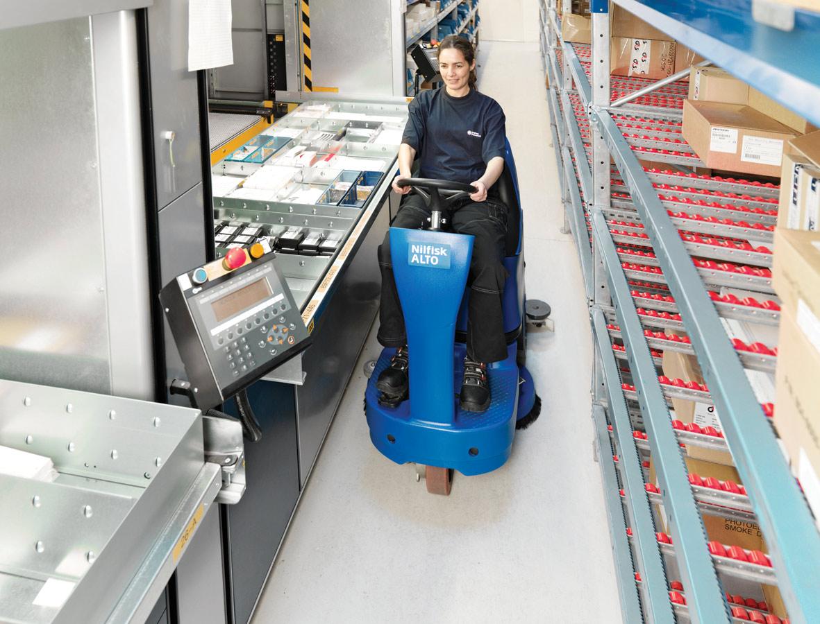 Frau auf Aufsitz-Kehrmaschine von Nilfisk-Alto